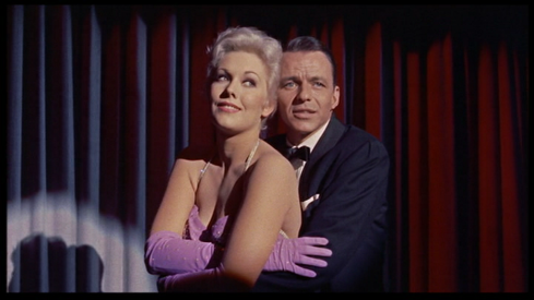 Frank Sinatra squeezes Kim Novak as he sings on stage in this frame from Pal Joey (1957)